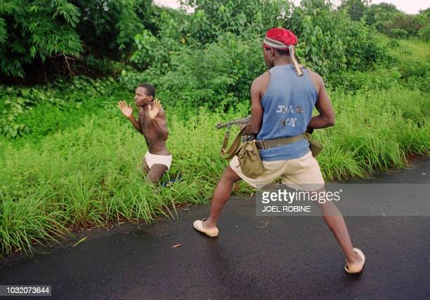 A rebel of Charles Taylor's National Patriotic Front of Liberia fire 03 August 1990 in Bentol on student William Weah executing his after roadside...