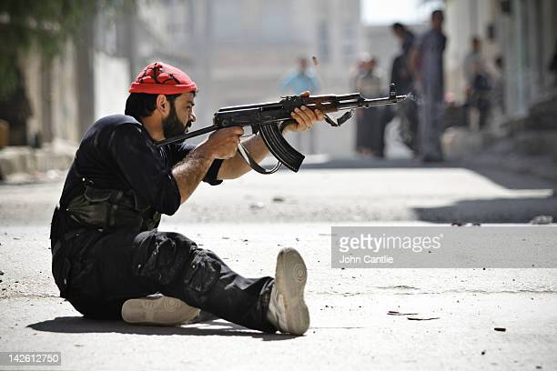 A rebel of the Free Syrian Army fires his Kalashnikov at government tanks that have advanced into Saraquib city on April 9 2012 in Syria Conitnuing...