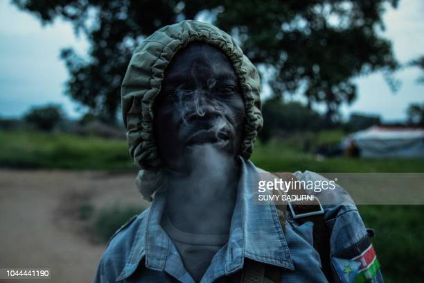 TOPSHOT A rebel of the Sudan People's Liberation MovementinOpposition a South Sudanese antigovernment force smokes a cigarette at a civilian base in...