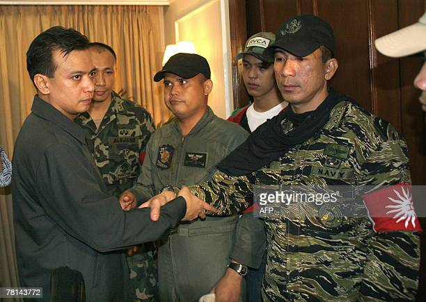 Rebel Philippine Senator Antonio Trillanes joins hands with rebel officer Lieutenant Senior Grade James Layug and others during their surrender to...