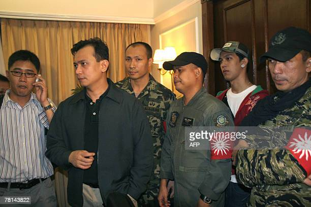 Rebel Senator and Navy Lieutenant Antonio Trillanes joined by rebel officers and civilian supporters gather inside a hotel room after announcing...