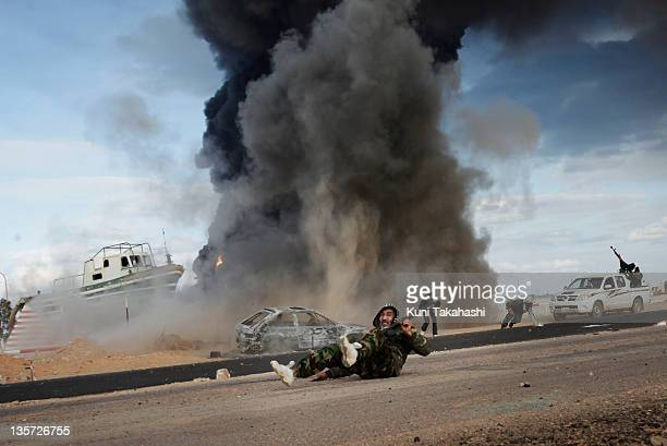 A rebel soldier fighting against Col Muammar Gaddafi lies on the ground after government forces dropped shells at the frontline March 9 2011 near Ras...