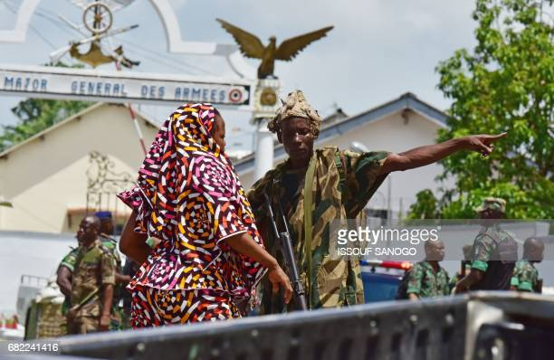TOPSHOT A rebel soldier gestures as he stands near the entrance of the Ivory Coast's army headquarters the Gallieni military camp in Abidjan on May...