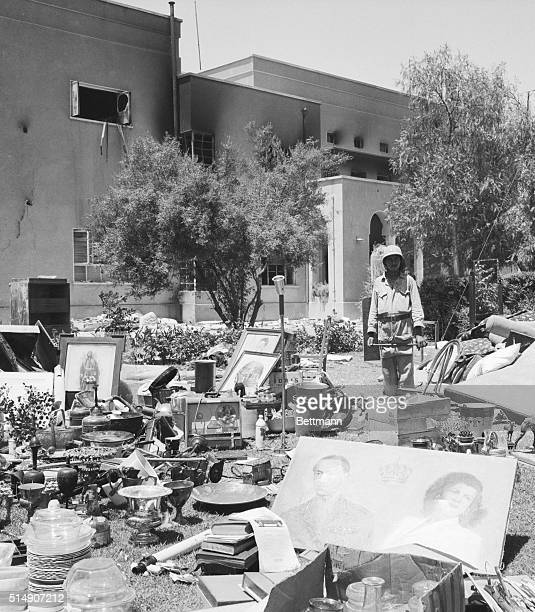 A rebel soldier stands on the lawn of the royal palace with possessions of the royal Iraqi family following a coup d'etat in which King Faisal and...