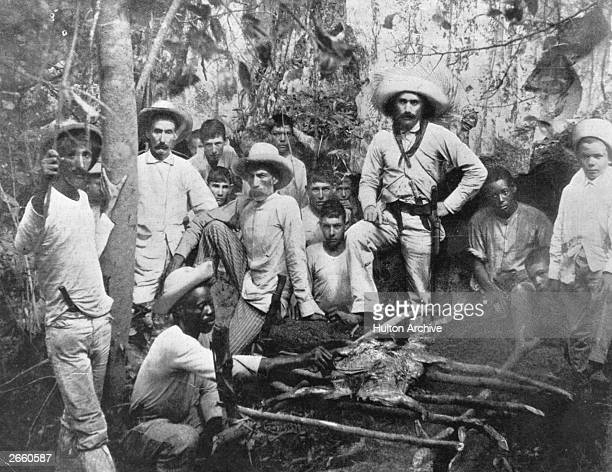 Rebel soldiers cook a pig for dinner at their camp during the insurrection of 1896 Cuba ceased to be a Spanish colony and gained independence after...
