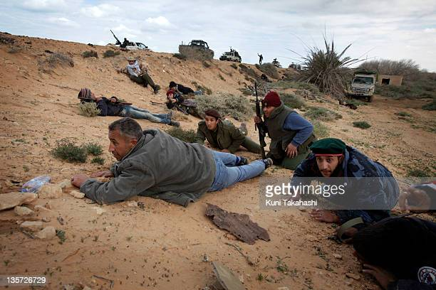 Rebel soldiers fighting against Col Muammar Gaddafi lay on the ground to take cover from shells dropped by the government force March 9 2011 near Ras...