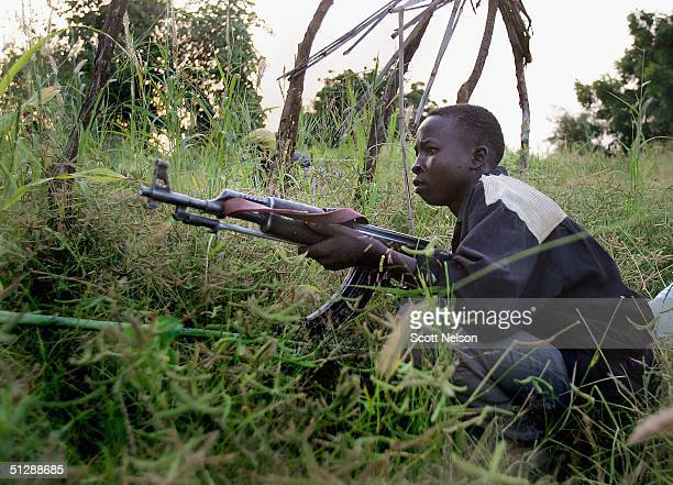 Rebel Sudanese Justice and Equality Movement fighter takes cover as suspected janjaweed militiamen pass nearby to their position while on patrol near...
