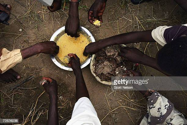 Rebel Sudanese Justice and Equality Movement fighters eat a very basic sauce and dough meal together at their base in the Darfur region of Sudan on...