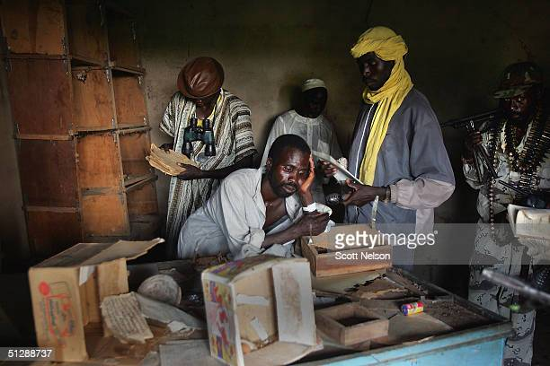 Rebel Sudanese Justice and Equality Movement fighters investigate an abandoned village that has been recently looted and burned by government...