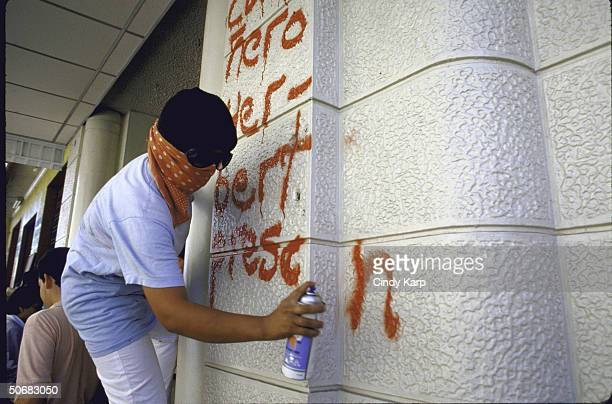 Rebel supporter spraying graffiti as part of protest during funeral march for slain Human Rights Comm president Herbert Anaya Sanabria