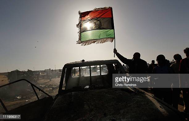 Rebel sympathizer holds the rebel flag over the charred remains of a Libyan army loyalist pickup truck bombed by NATO forces April 10, 2011 on the...