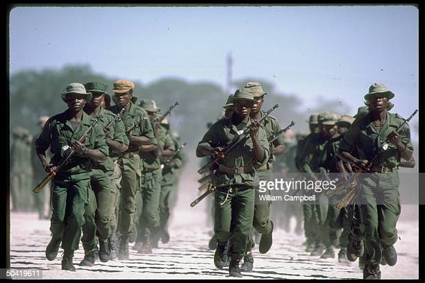 UNITA rebel troops in fatigues carrying guns and jogging in rows in area of UNITA HQ