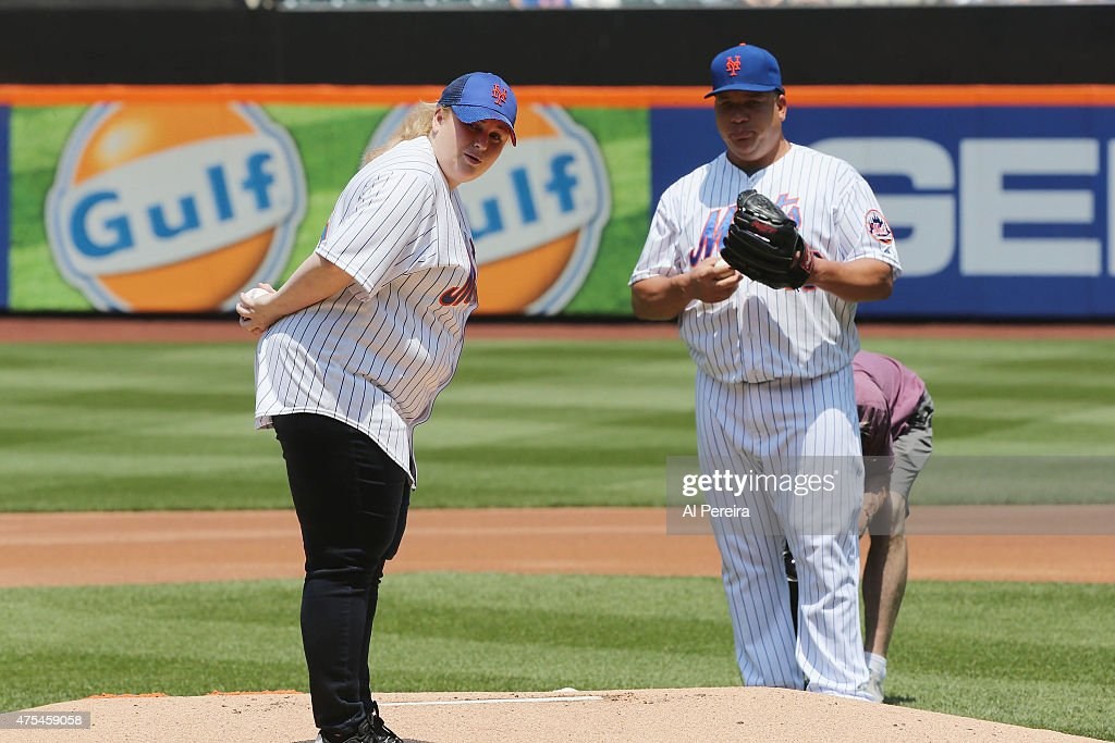 Rebel Wilson is watched by New York Mets Pitcher Bartolo Colon #40 when she throws out the first pitch when she attends the New York Mets vs Miami Marlins game at Citi Field on May 31, 2015 in New York City.