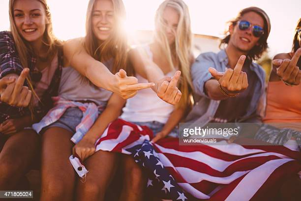 rebellious teens showing their middle fingers and holding american flag - obscene gesture stock photos and pictures