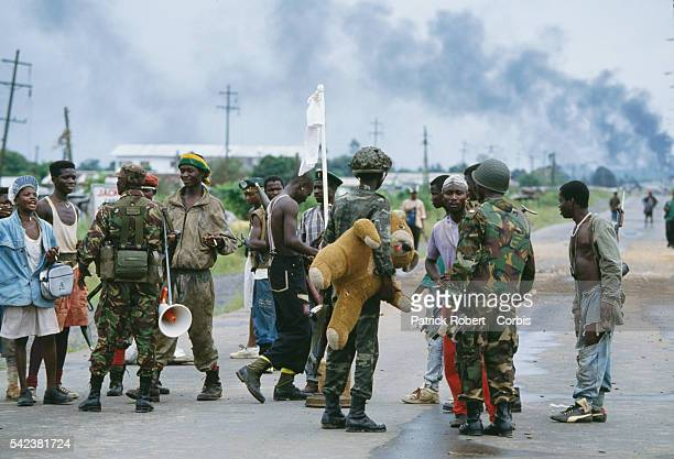 Rebels and ECOMOG soldiers chat on a road in Monrovia during the Liberian Civil War One NPFL rebel brandishes a white flag while an ECOMOG soldier...
