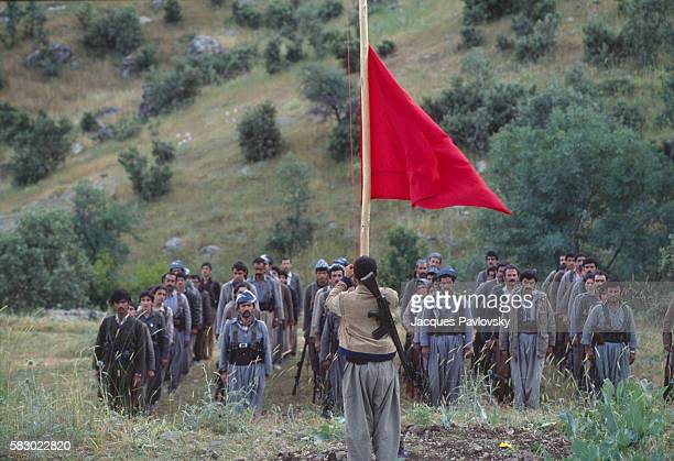 Rebels belonging to the MarxistLeninist group Komala raise a red flag in the mountains of the Iraqi Kurdistan