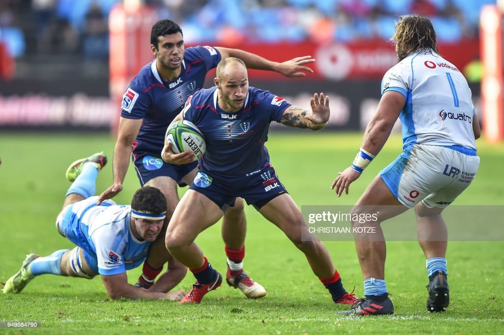 Rebels' Billy Meakes (2nd R) runs as Bulls' Marco van Staden (L) dives to tackle him during the Super Rugby rugby union match between South Africa's Bulls and Australia's Rebels at the Loftus Versfeld Stadium in Pretoria on April 21, 2018.