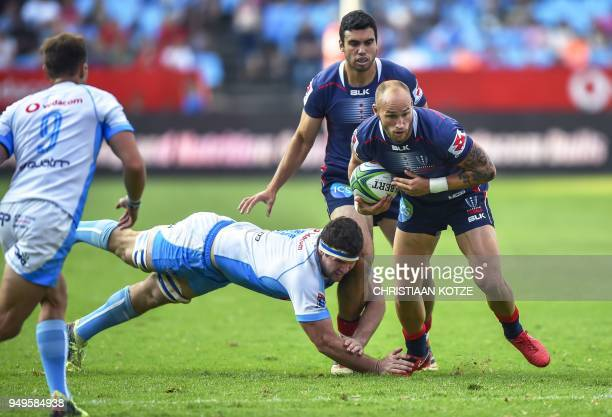 Rebels' Billy Meakes runs as Bulls' Marco van Staden tackles during the Super Rugby rugby union match between South Africa's Bulls and Australia's...