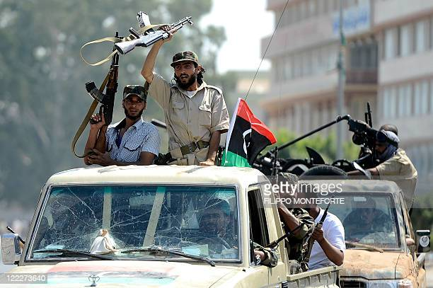 Rebels celebrate after the southwestern neighbourhood of Tripoli was taken over on August 27 as neighbourhoods in the capital slowly fell from the...