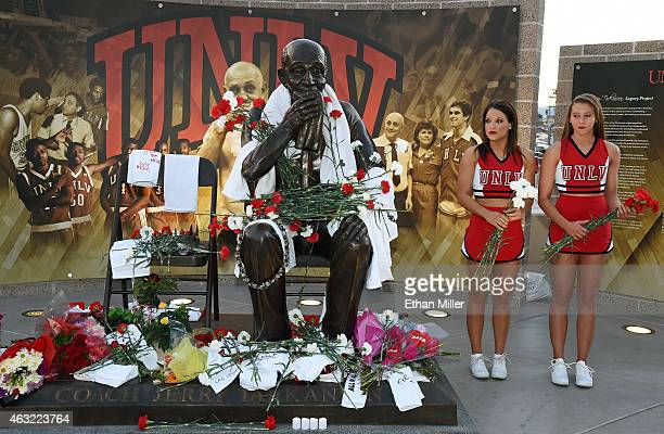 Rebels cheerleaders hold carnations at a statue of Jerry Tarkanian outside the Thomas Mack Center at UNLV during a gathering of fans for the Naismith...