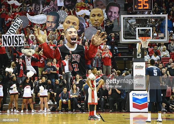 Rebels fans use Khem Kong a large prop of Khem Birch of the UNLV Rebels to try to distract Jarred Shaw of the Utah State Aggies as he shoots a free...