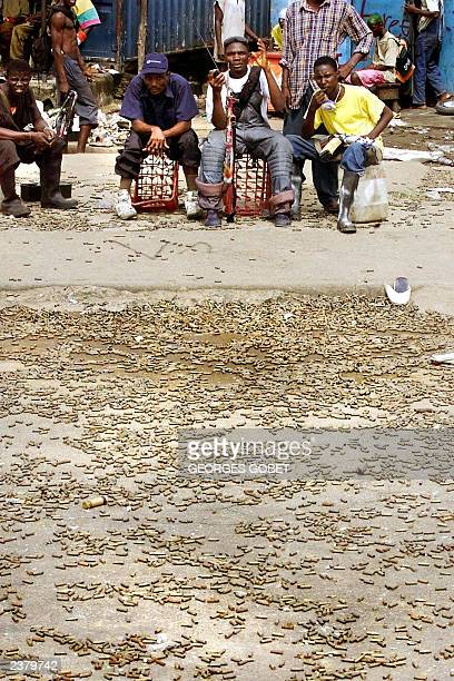 Rebels from Liberians United for Reconciliation and Democracy signal to the photographer as they sit in a street littered with bullet casings 05...