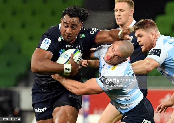 Rebels' Pone Faamausili shrugs off the tackles of Waratahs' Carlo Tizzano and Lachlan Swinton during the Super Rugby Australia match between the...