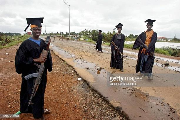 rebels pose for photographers in front of Stocktone Creek bridge northeastern Monrovia where combats have ceased for 48 hours 06 August 2003 The area...
