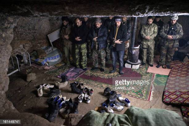 Rebels pray inside a cave in the village of Kfarruma in the flashpoint Syrian province of Idlib near the border with Turkey on February 10 2013 The...