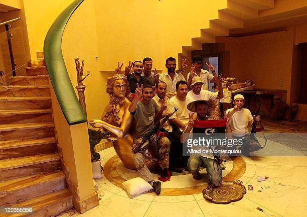 Rebels sit on the large gilded sofa in the entrance of Aisha Gaddafi's luxury villa on August 27 2011 in Tripoli Libya Houses belonging to the Libyan...