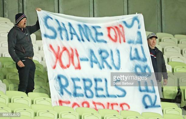 Rebels supporters in the crowd hold a sign aloft which reads 'Shame on you ARU Rebels forever' during the round eight Super Rugby match between the...