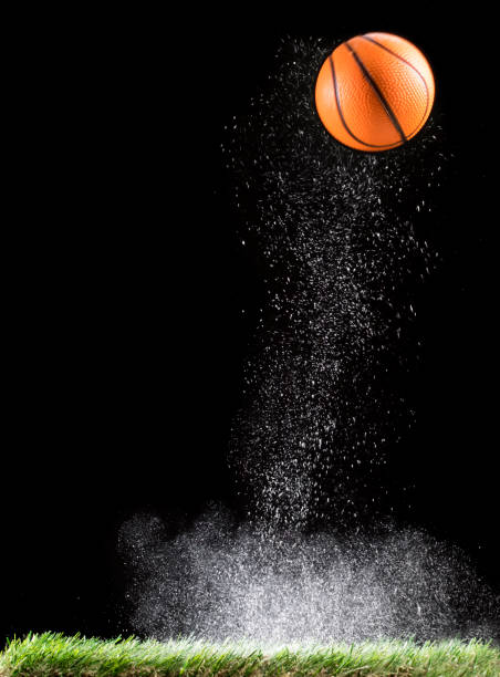 Rebound of a ball of basketball for the impact on a surface of lawn, of an field of game, with ascending powder