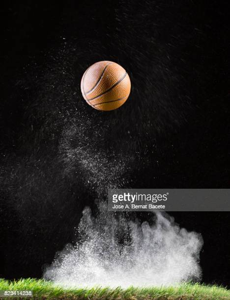 rebound of a ball of basketball for the impact on a surface of lawn, of an field of game, with ascending powder - basketball stadium stock photos and pictures