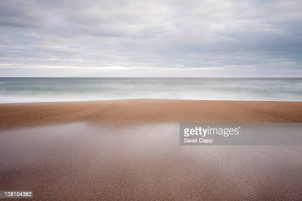 receding waves on overcast day at coumeenoule beach, dingle peninsula, dingle, republic of ireland - seascape stock pictures, royalty-free photos & images
