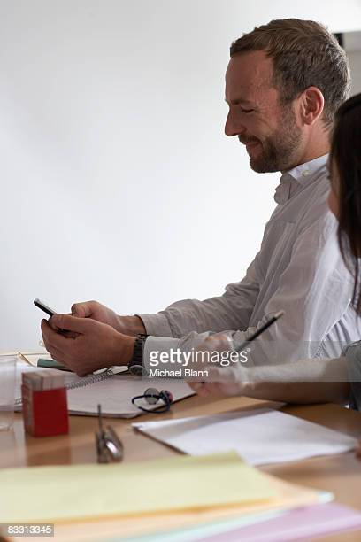 receiveing texto during a meeting - texto stock photos and pictures