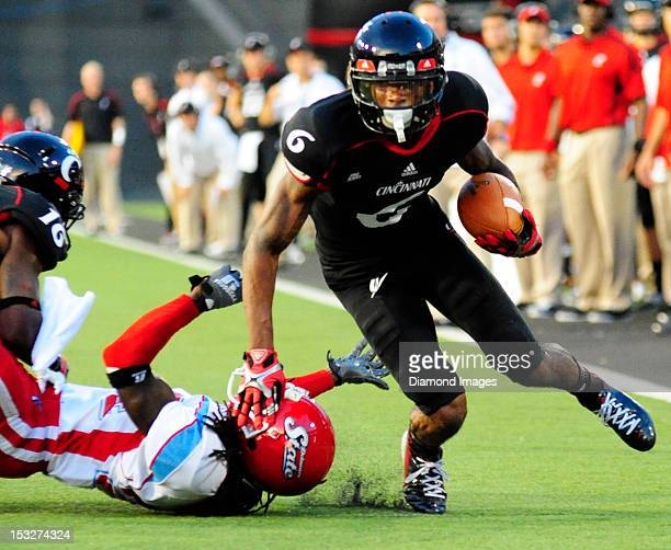 Receiver Anthony McClung of the Cincinnati Bearcats slips a tackle and heads to the endzone during a game with the Delaware State Hornets at Nippert...