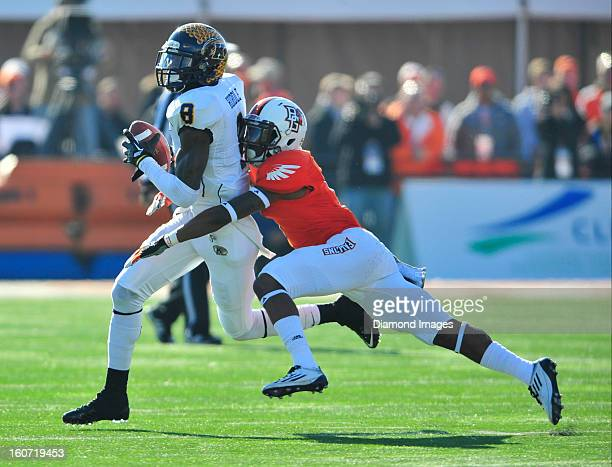 Receiver Calvin Tiggle of the Kent State Golden Flashes is tackled by defensive back Cameron Truss of the Bowling Green Falcons during a game with...