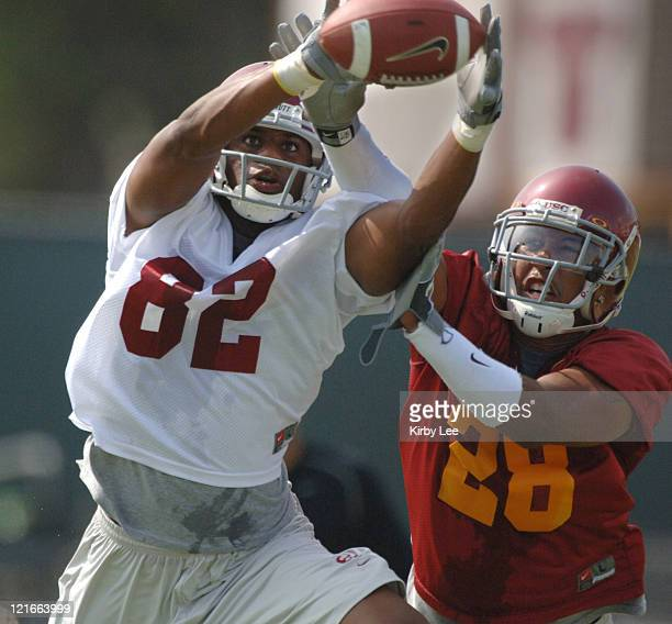 Receiver Chris McFoy makes a reception despite the defensive efforts of cornerback Terrell Thomas during the first day of fall practice at Howard...