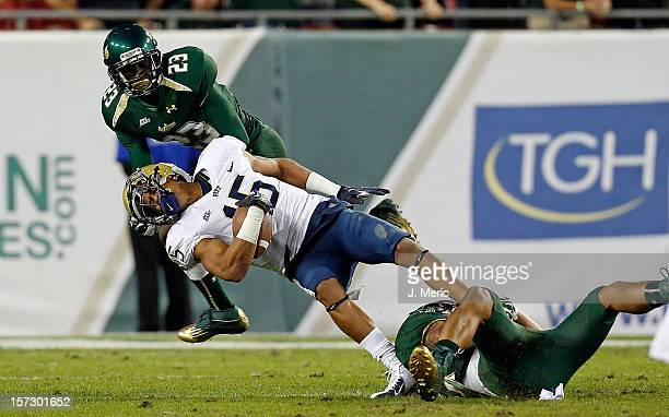 Receiver Devin Street of the Pittsburgh Panthers is taken down by defenders Mark Joyce and Kenneth Durden of the South Florida Bulls during the game...