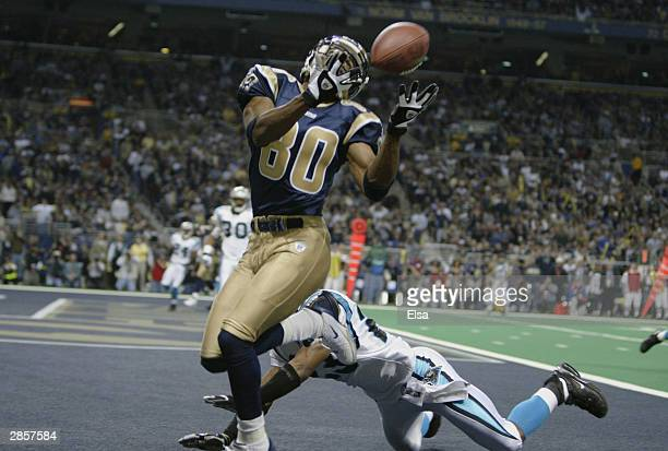 Receiver Isaac Bruce of the St. Louis Rams lets a touchdown pass goes through his hands in front of cornerback Reggie Howard of the Carolina Panthers...