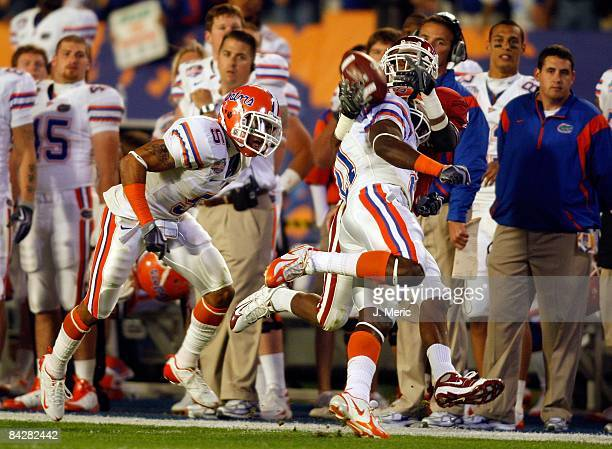 Receiver Manuel Johnson of the Oklahoma Sooners is separated from the ball by safety Major Wright of the Florida Gators during the FedEx BCS National...