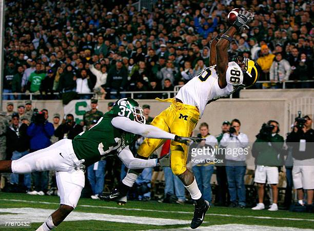Receiver Mario Manningham of the Michigan Wolverines pulls in the gamewinning touchdown against cornerback Ross Weaver of the Michigan State Spartans...