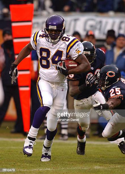 Receiver Randy Moss of the Minnesota Vikings pulls away from safety Bobby Gray and cornerback Charles Tillman of the Chicago Bears on a touchdown run...