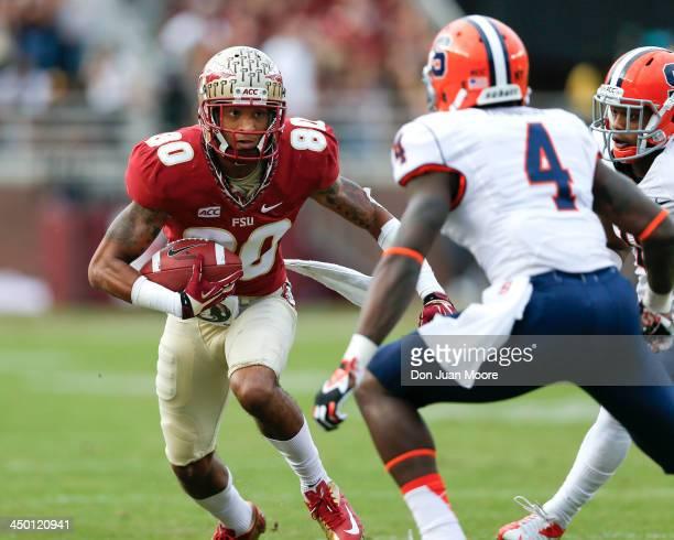 Receiver Rashad Greene of the Florida State Seminoles makes a pass play against cornerback Brandon Reddish of the Syracuse Orange at Doak Campbell...