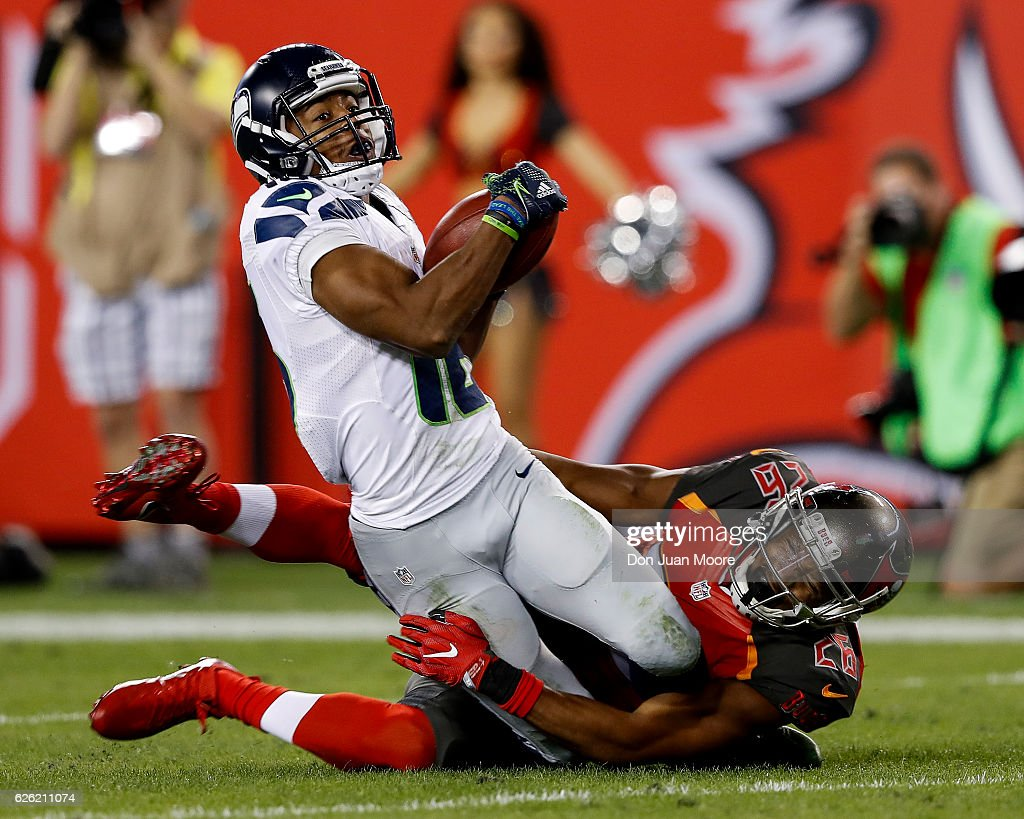 Receiver Tyler Lockett #16 of the Seattle Seahawks is tackled by Cornerback Josh Robinson #26 of the Tampa Bay Buccaneers on a punter return at Raymond James Stadium on November 27, 2016 in Tampa, Florida. The Bucs defeated the Seahawks 14 to 5.