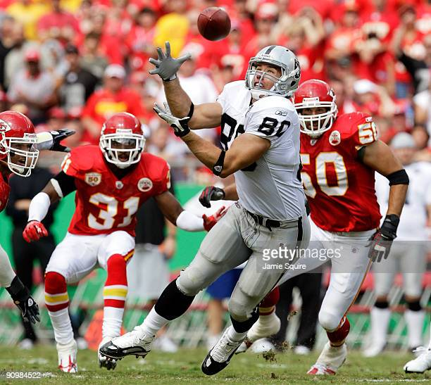 Receiver Zach Miller of the Oakland Raiders makes a catch as Maurice Leggett and Mike Vrabel of the Kansas City Chiefs defend during the game at...