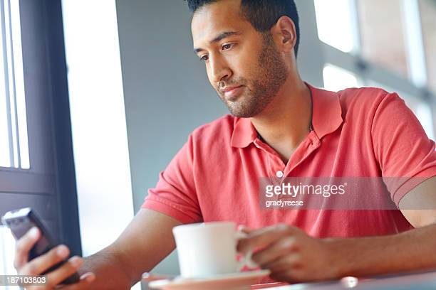 Receiving a text on his coffee break