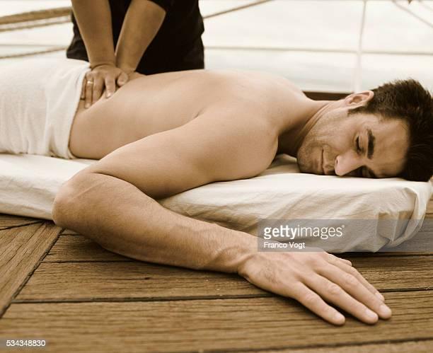 receiving massage on deck of ship - massaggio sensuale foto e immagini stock