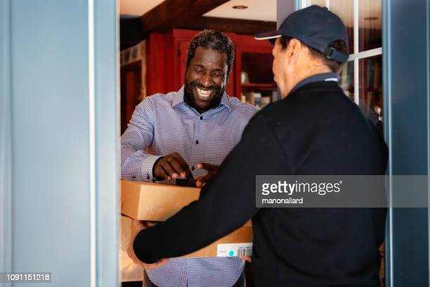 receiving online shopping from delivery man - postal worker stock pictures, royalty-free photos & images