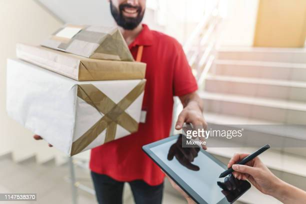 receiving parcels at the doorstep - endopack stock pictures, royalty-free photos & images
